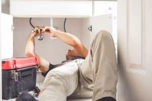 Image of man fixing plumbing issues